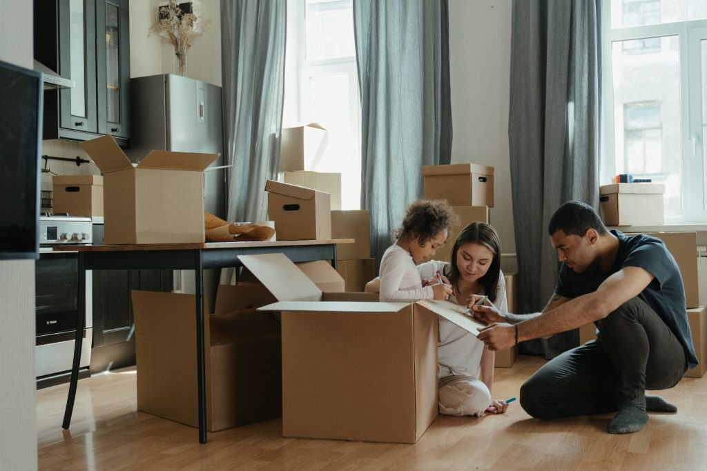 (alt-text: A family packs up moving boxes and checks a moving house checklist to make sure they have everything.)