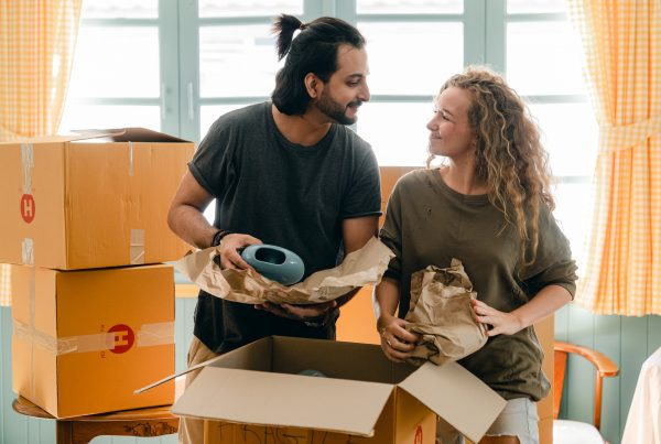 (alt-text: A man and woman work on packing belongings together for moving into a new house.)