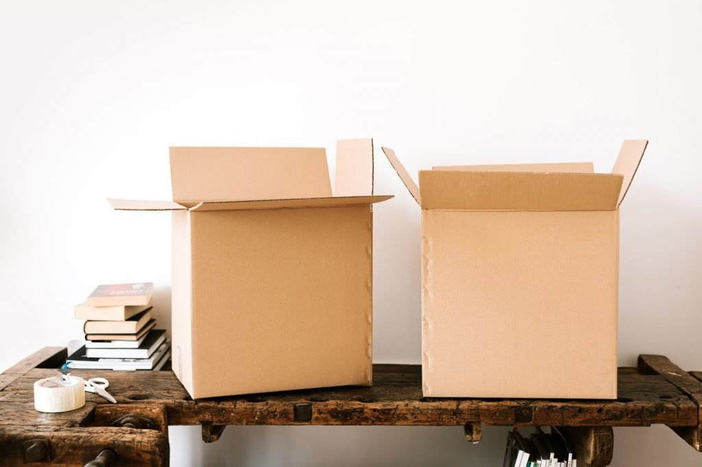 <two boxes on a table with books, packing table and a scissors>