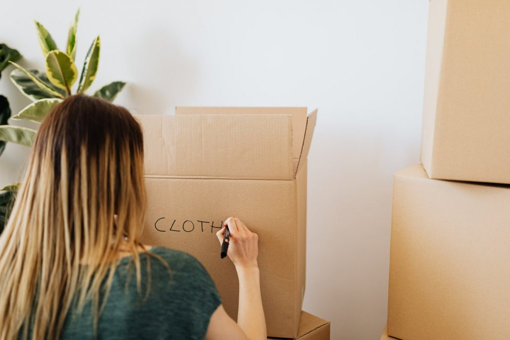 """<woman labelling two boxes with the word """"clothes"""">"""
