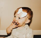 little girl with cheeky smile eating cake off her fingers