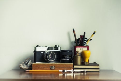 Stack of items on a desk including camera, notebooks, and pencil holder