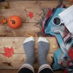 Feet in wool socks standing on a wooden step with coffee cup, book, and gourd