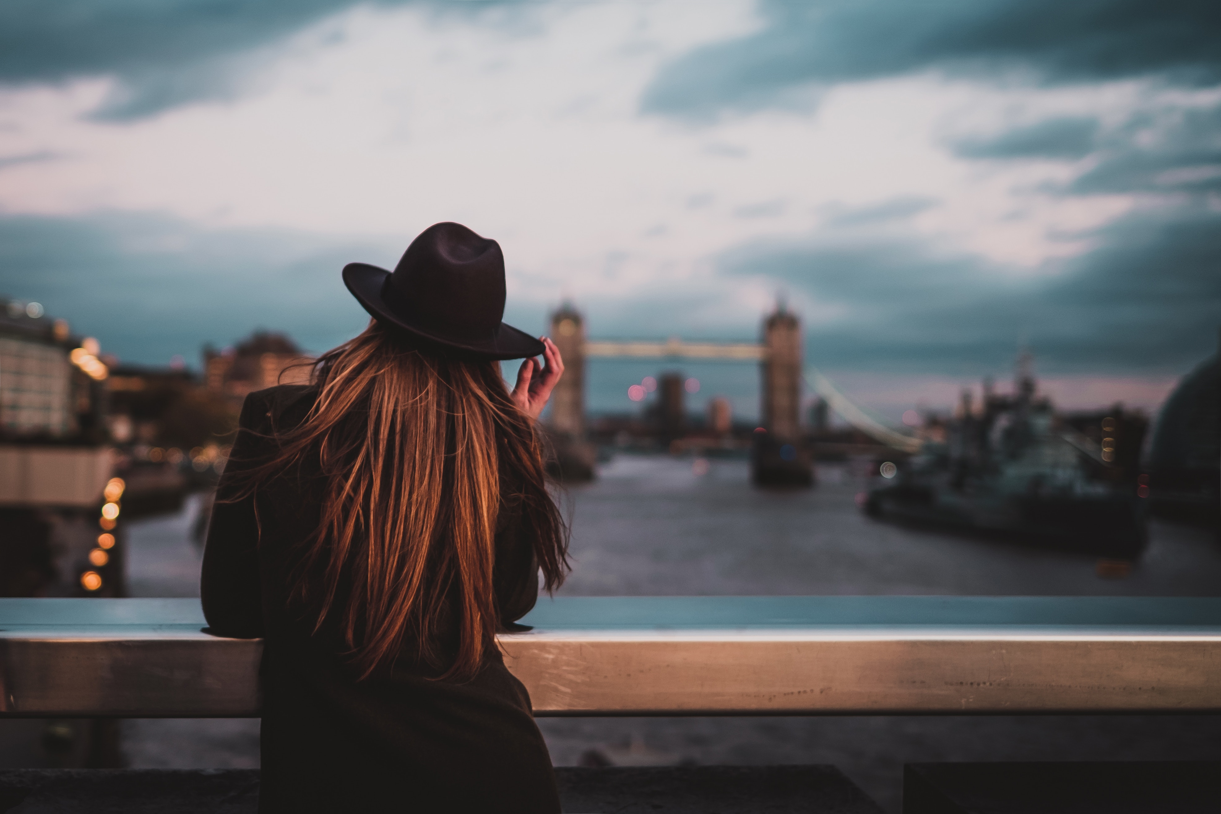 Back of woman wearing a fedora looking out over London