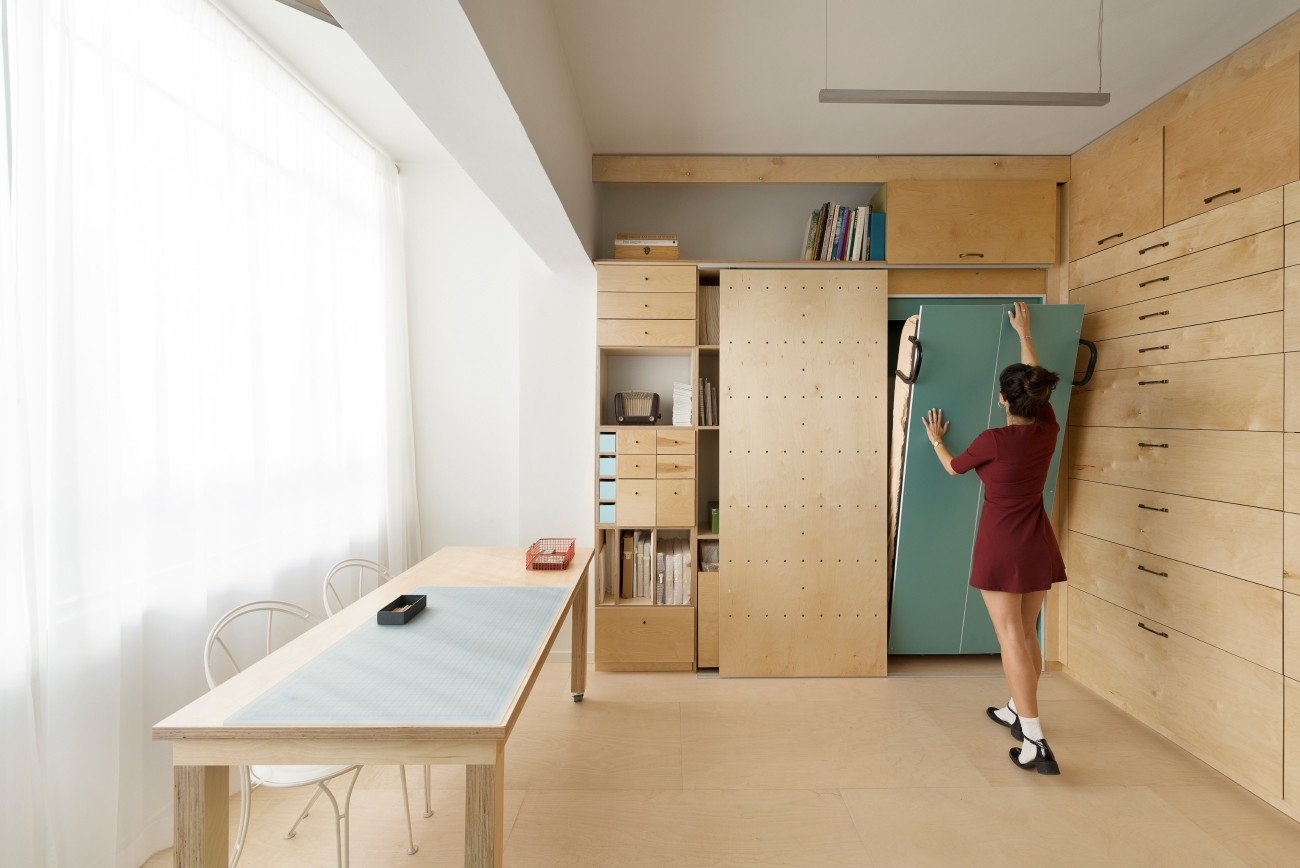 Woman folding away a bed into the wall of her apartment