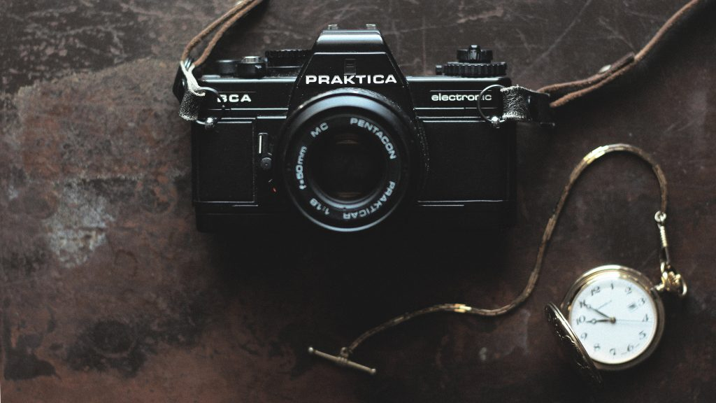 Camera and pocket watch on hardwood background