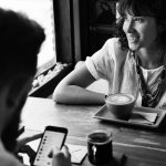 Grayscale photo of woman drinking coffee with man