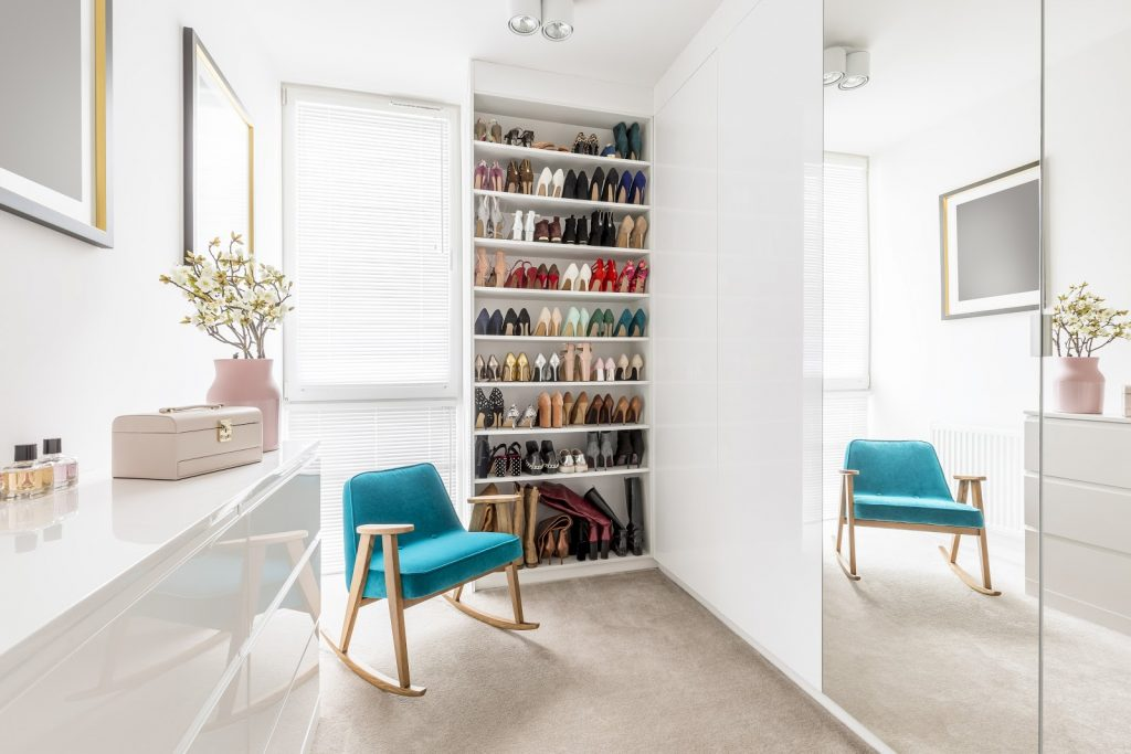<walk in wardrobe with chair, mirror, drawers and shoe storage>