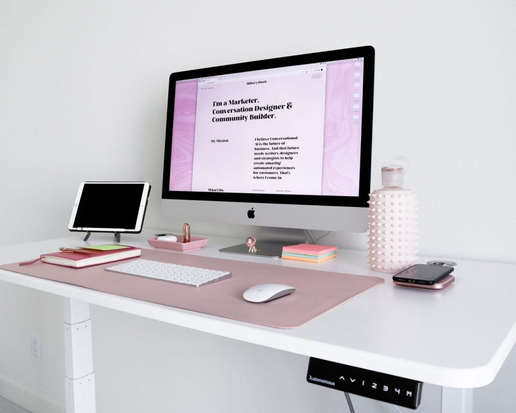 <tablet, computer, water bottle, and accessories on a motorised standing desk>