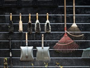 <view of garden tools organised on the wall of a garden shed>