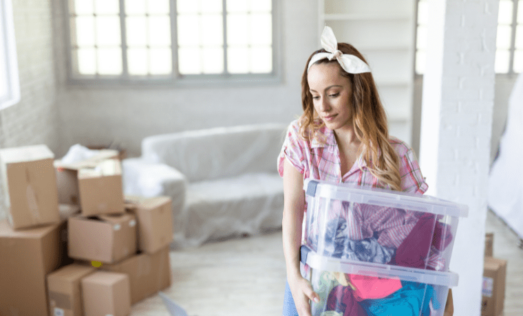 Female student holding moving boxes with cardboard boxes in the background.
