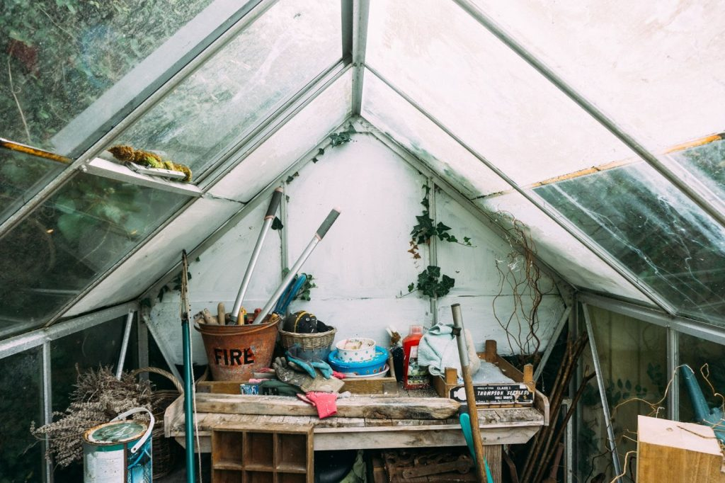 <interior view of a garden shed with a cluttered table>